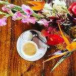 latte with flowers on table - happy hour at cafe des amis paia maui