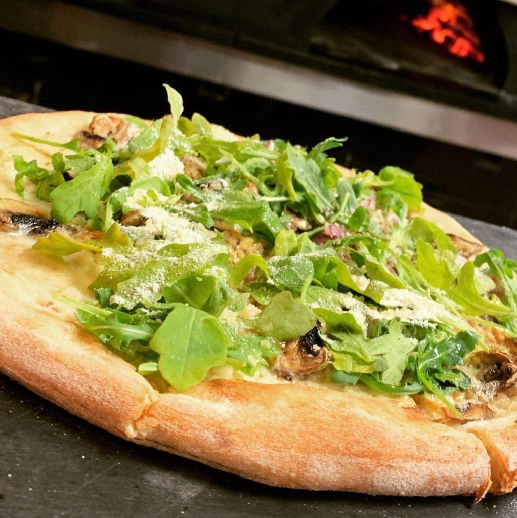 brick oven pizza with mushrooms and arugula at pi artisan pizzeria lahaina maui hawaii