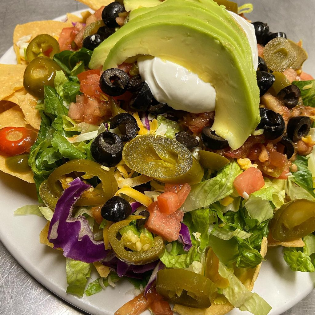 happy hour mexican tostada with avocado and sour cream