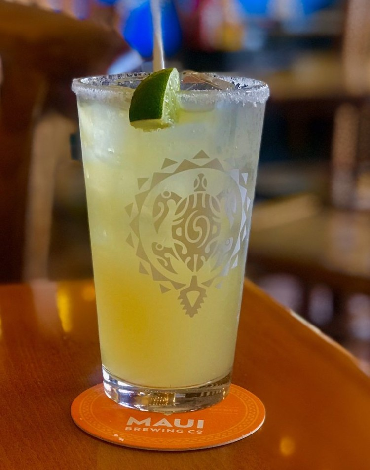 Happy hour margarita with lime in a Maui Brewing glass