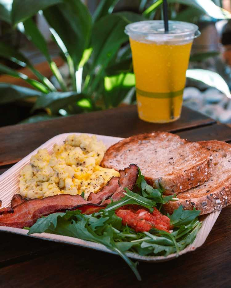 Delicious breakfast plate - bacon, scrambled eggs, whole-grain toast, and greens at Paia Maui Hawaii restaurant