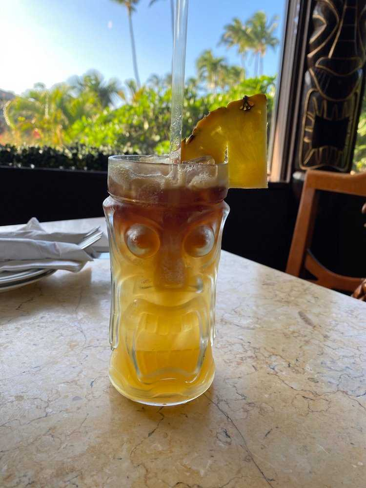 Happy Hour Mai Tai Tropical Cocktail in Tiki Glass with Pineapple Garnish in Maui Hawaii